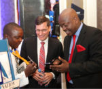 Visa Sub Saharan Africa Group Country Manager Andrew Torre (centre), demonstrates how the M Visa app works to KCB Group Head of  Channels Retail Banking Dennis Njau (right), Looking on is newspaper vendor Humphrey-1