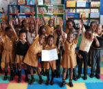 School children receive books produced by Canon for Room to Read literacy program.